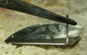 Tweezers act as a heat sink and protect fragile ear post.